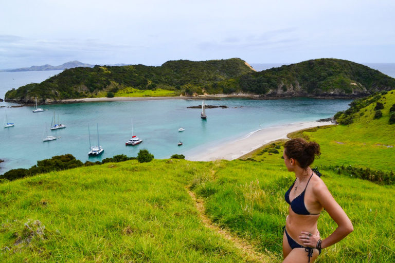 girl in bikini standing on green hill with bay in background