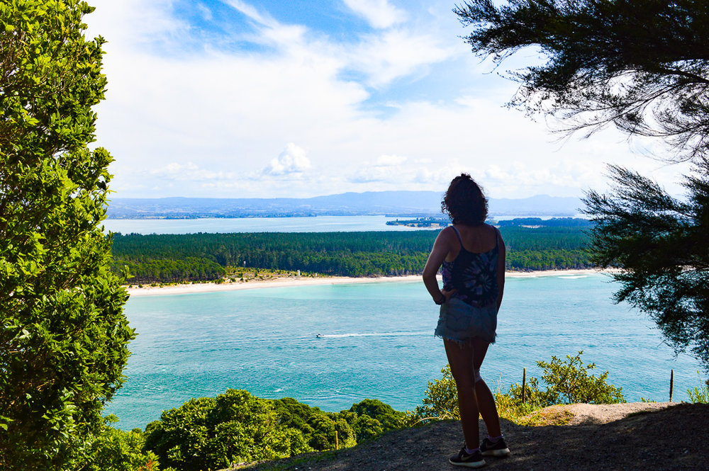 girl posing in front of sea on a hill surrounded by trees