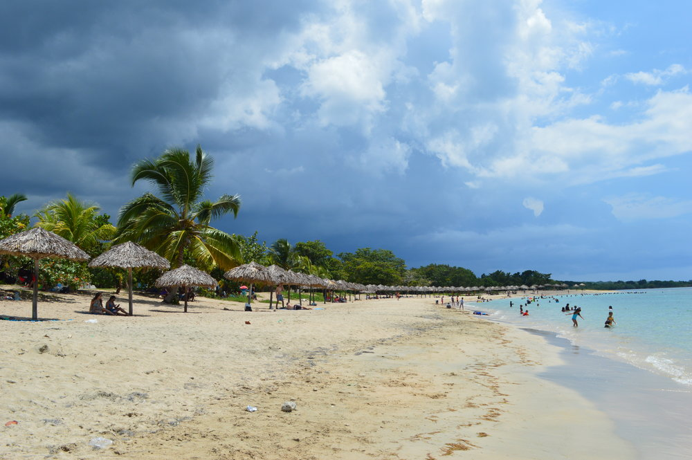 Cuban beach with palm parasols and stormy sky