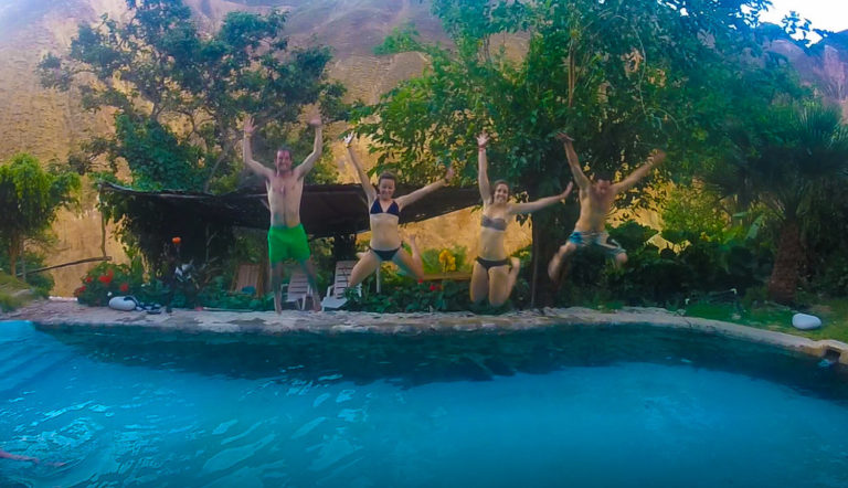 jumping into a swimming pool at the colca canyon oasis homestay