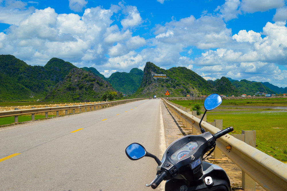 motorbike parked by side of road with mountains in the background in vietnam