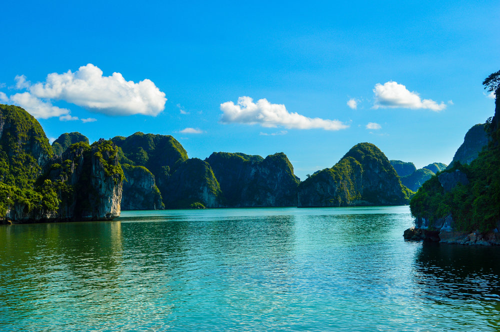 boats on blue water with green limestone turrets