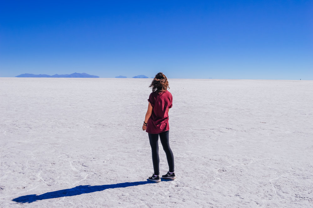 girl in red top standing on white endless salt flats