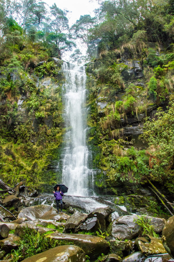 tall waterfall with jungle ferns and girl standing with an umbrella