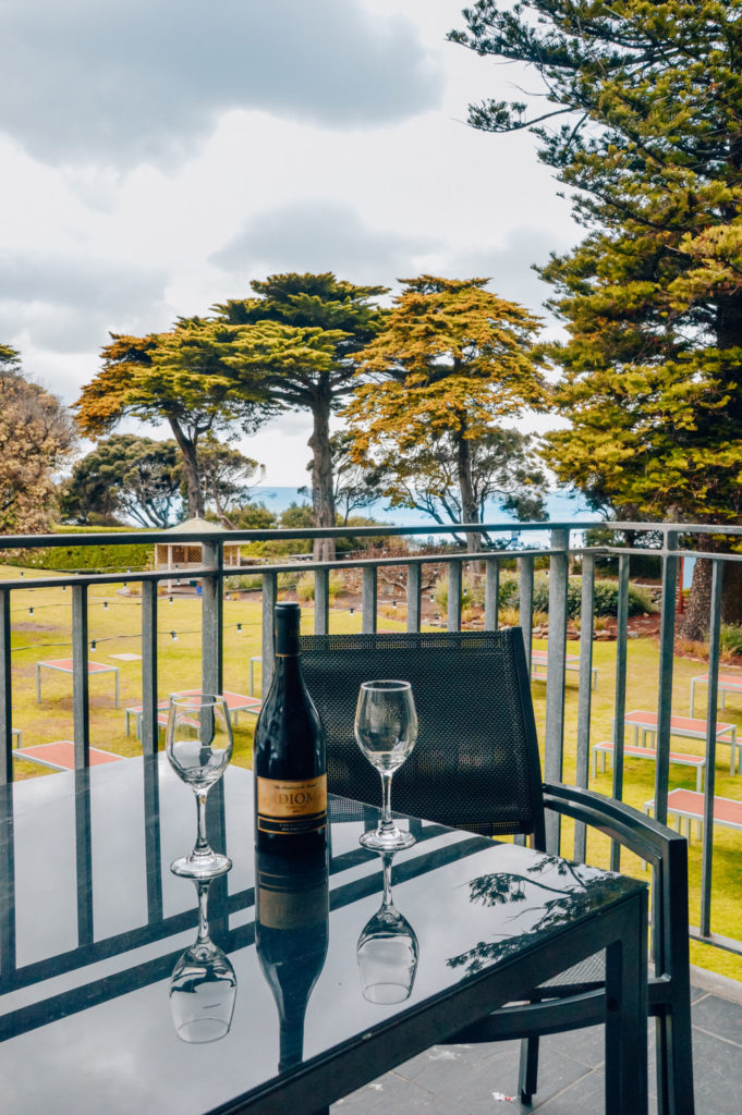bottle of wine and glasses on black table on balcony with tree background