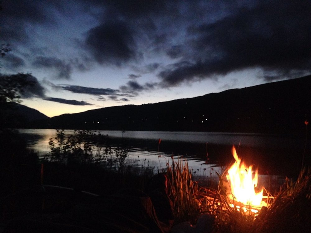 camp fire at nigh beside lake