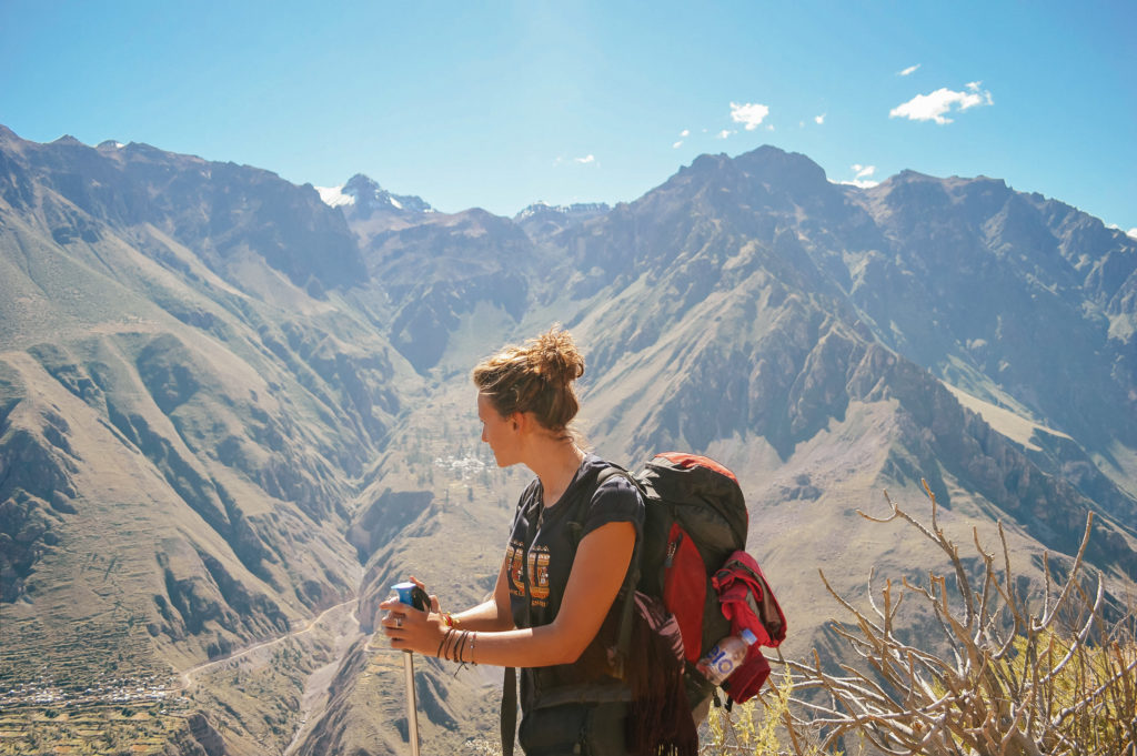 girl with backpack with mountain canyon in background
