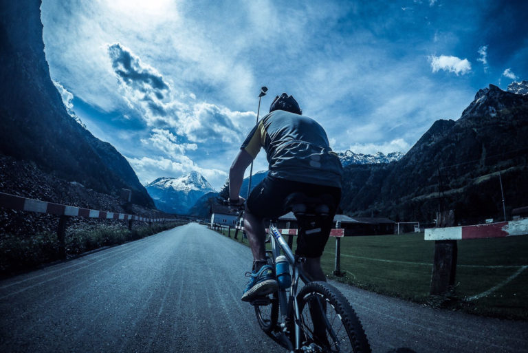 man cycling on bike with moutains as backdrop