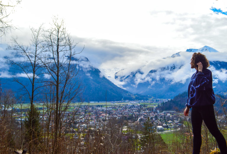 girl standing alone with a backdrop of mountains in Switzerland