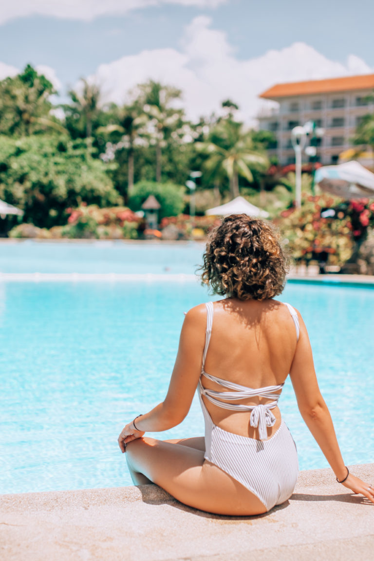 girl in swimsuit sitting on edge of swimming pool