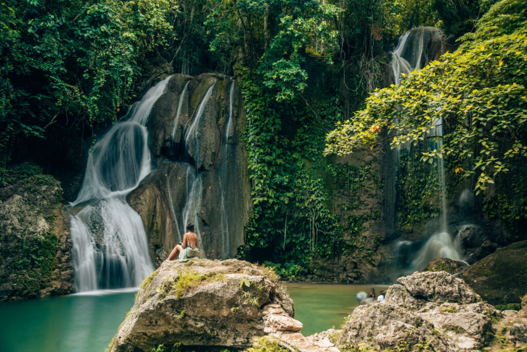 girl sat on rock in front of waterfall and lagoon in asia