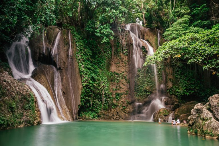 jungle waterfall flowing into pale green pool