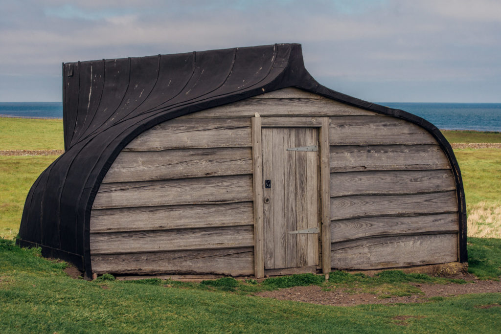wooden boat shed on grass