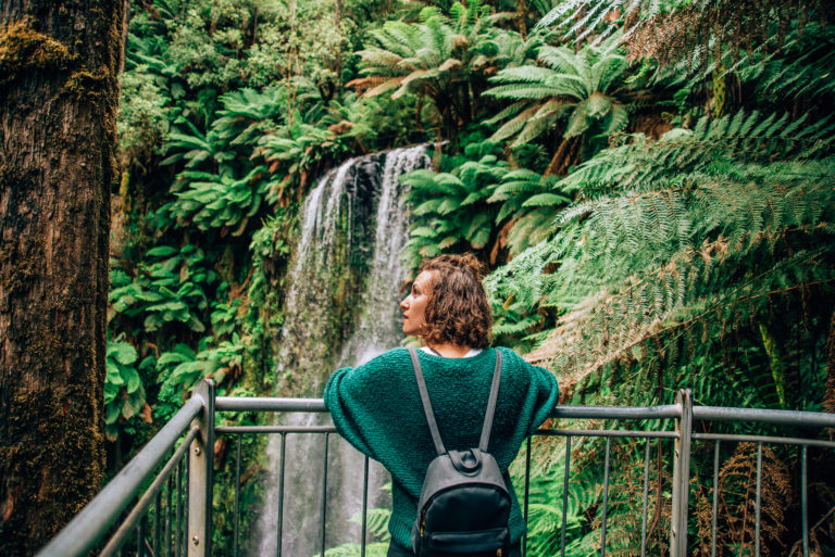 girl standing in front of waterfall in the otways rainforest