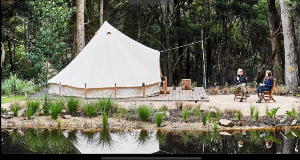 bell tent by pond with a backdrop of trees