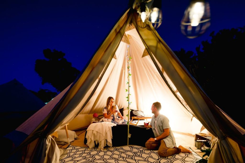 couple inside glamping tent at night
