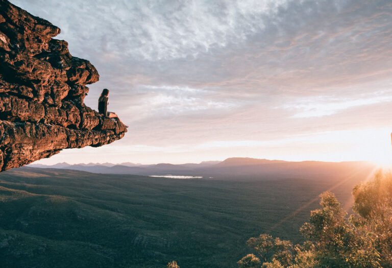 girl sitting on rock ledge overlooking sunset and trees