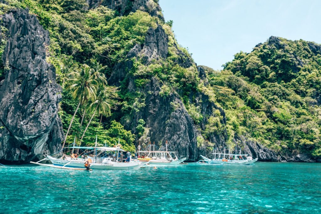 small boats on aqua marine water against rocky cliff with vegetation in the Philippines
