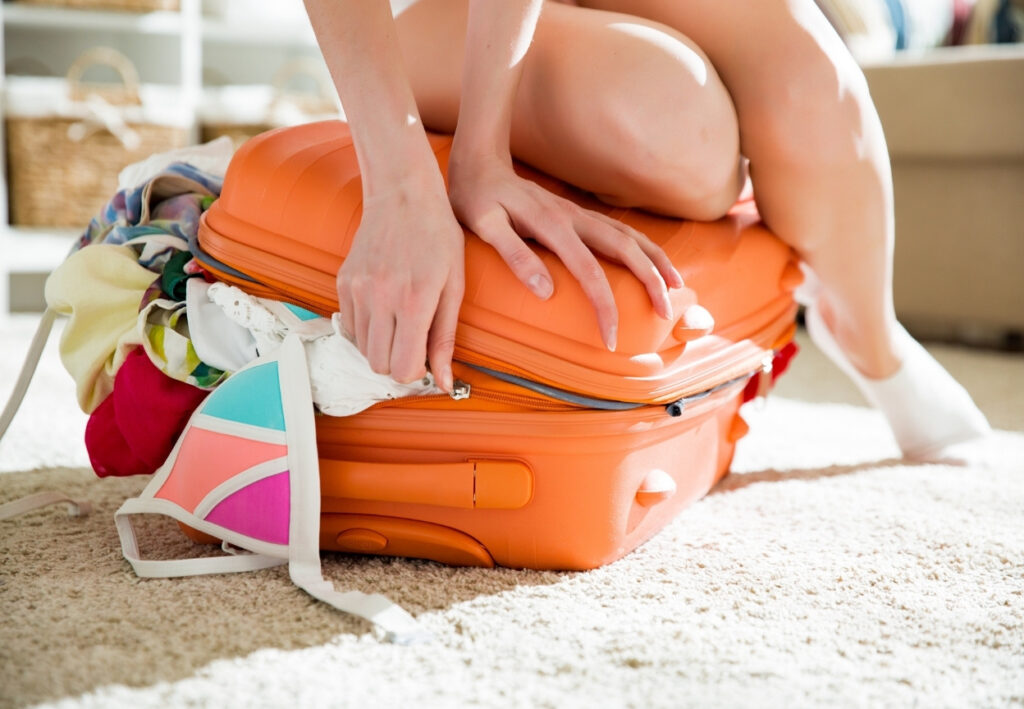 girl sat on overflowing suitcase