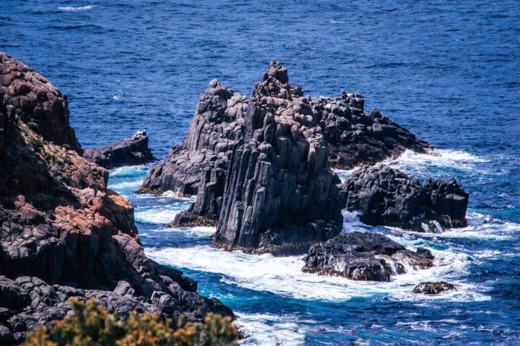 dolerite rock formations sticking out from the sea with white sea spray