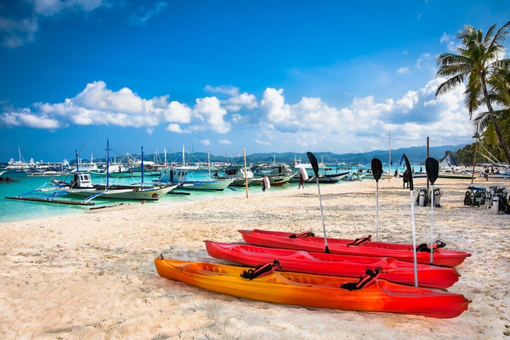 red canoes and boats on the water at Bulabog Beach Boracay