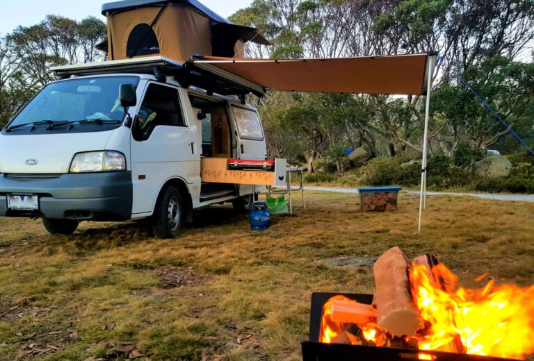 fire in front of small camper van with awning