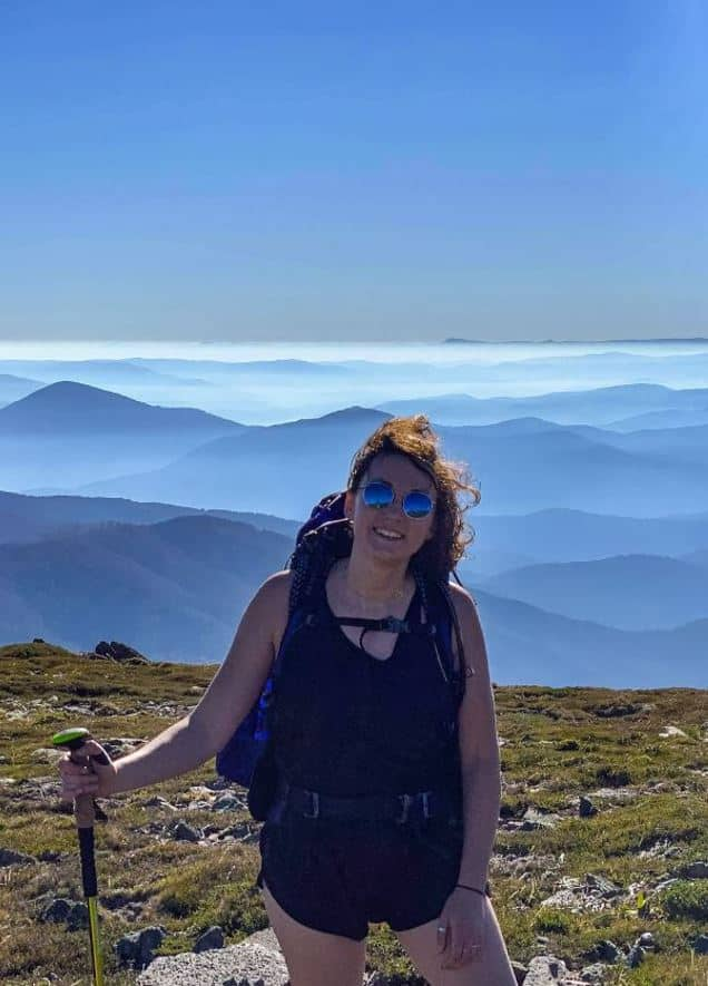 solo woman standing on top of a mountain with cloud covered mountain range in the background